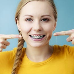 Woman pointing to her smile with braces