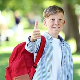Young boy with braces giving thumbs up