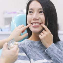 A woman pointing at her smile at a dental office.