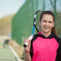 A young girl holding a tennis racket and wearing braces