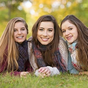 Three young women smiling together outdoors