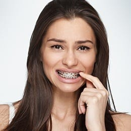Woman with braces pointing to teeth