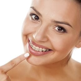 Woman in braces pointing at her smile