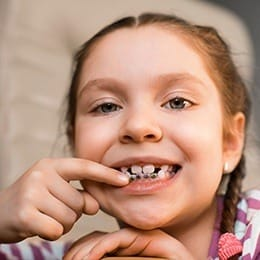 Little girl pointing to her orthodontic appliance