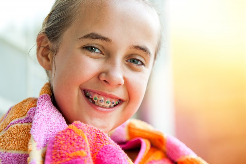 Girl in pink and orange smiling with braces